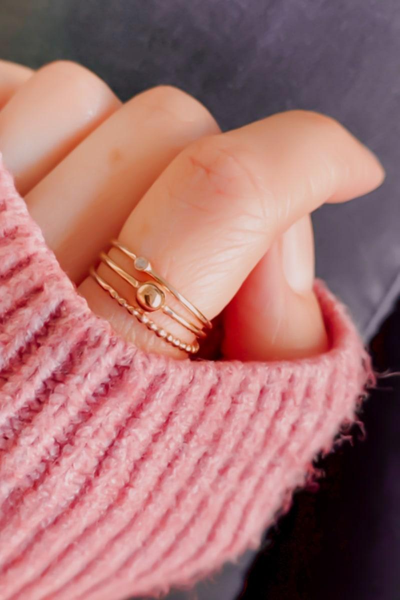 Bild von Frau mit rosa Pullover und Ring aus Ihrer eigenen Schmuckkollektion